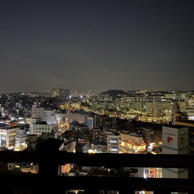 Ausblick von einem Park auf die glitzernde Stadt bei Nacht