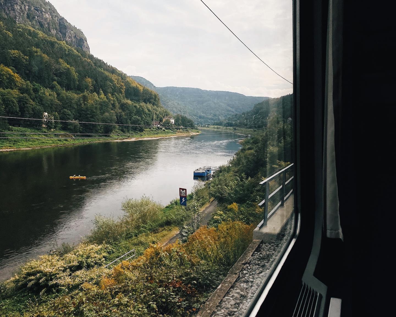 Blick aus dem Zugfenster auf einen Fluss und Berge