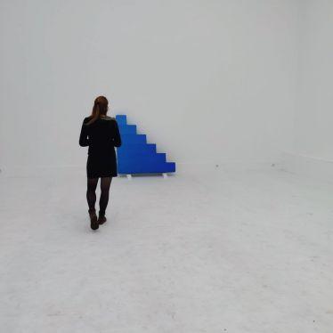 Heller leerer Raum mit einer blauen Treppe an der Wand.