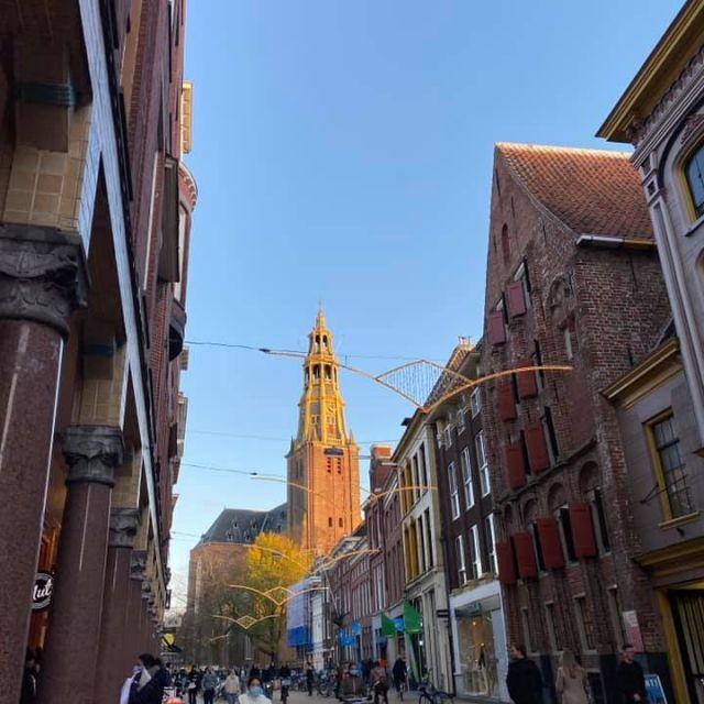 Man sieht eine belebte Einkaufsstraße. Auch hier ist der Martinitoren zu sehen. Er wird vom Licht der Abendsonne angestrahlt.