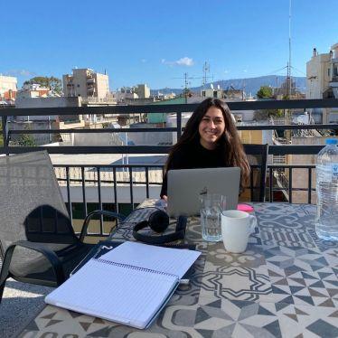 Auf dem Bild sieht man, wie ich mit meinem Laptop und Schreibmaterialien und einer Tasse Kaffee am Balkontisch sitze. Auf dem Tisch liegen ebenfalls Kopfhörer. Im Hintergrund ist ein strahlend blauer Himmel und die Hochhäuser des Stadtviertels Egaleo sind zu sehen.
