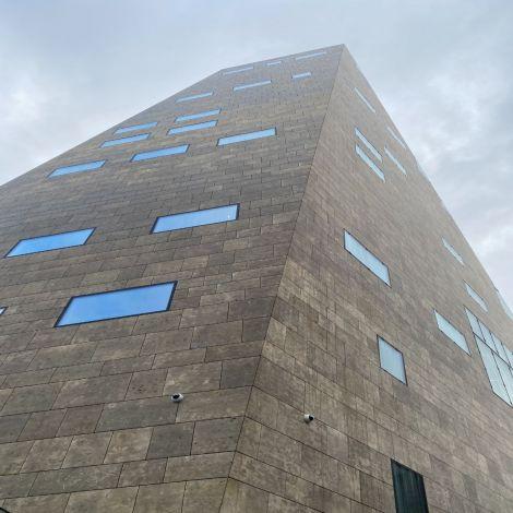 Hier sieht man das Forum von außen. Es ist ziemlich groß und streckt sich in den Himmel. Die Farbe ist braun gräulich, die Fenster sind relativ willkürlich angebracht.