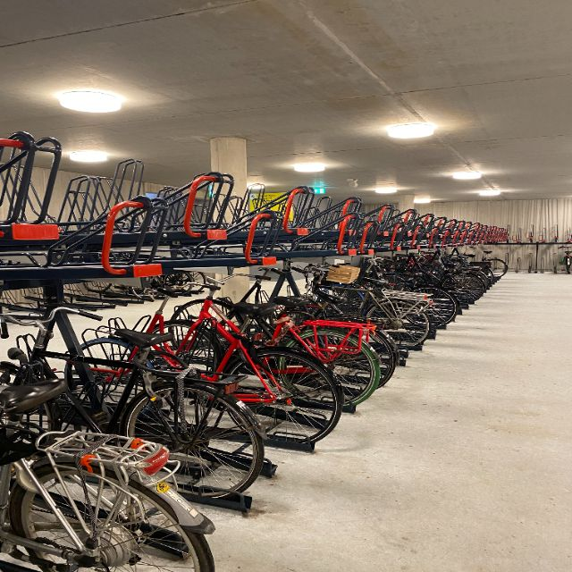 """Man erkennt die Fahrradtiefgarage. Ulkig daran ist, dass man hier die Fahrräder tatsächlich zweigeschossig stapeln kann. Man kann ein Fahrradreck aus dem oberen """"Regal"""" hinausziehen und dann kann das Fahrrad auch oben aufbewahrt werden. Das ist sehr flächeneffizient."""