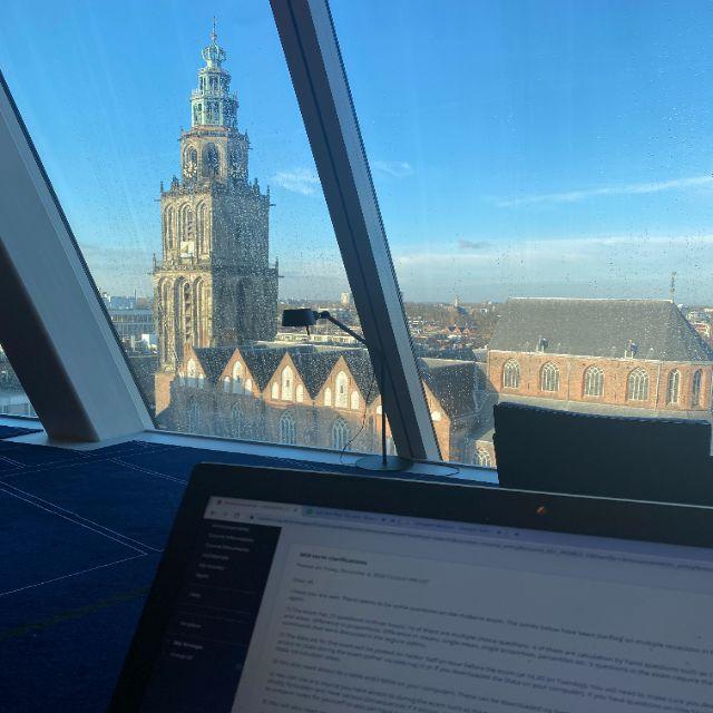 Der Fotograph sitzt mit seinem Laptop vor einer großen Fensterfront. Der Blick ist gut auf den großen Kirchturm der Stadt gerichtet.