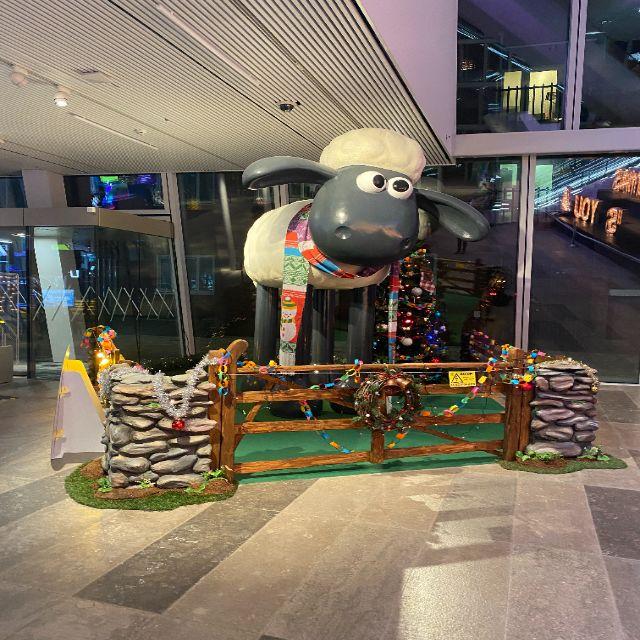 Hier sieht man eine riesige Figur von Shaun das Schaf, weihnachtlich geschmückt.