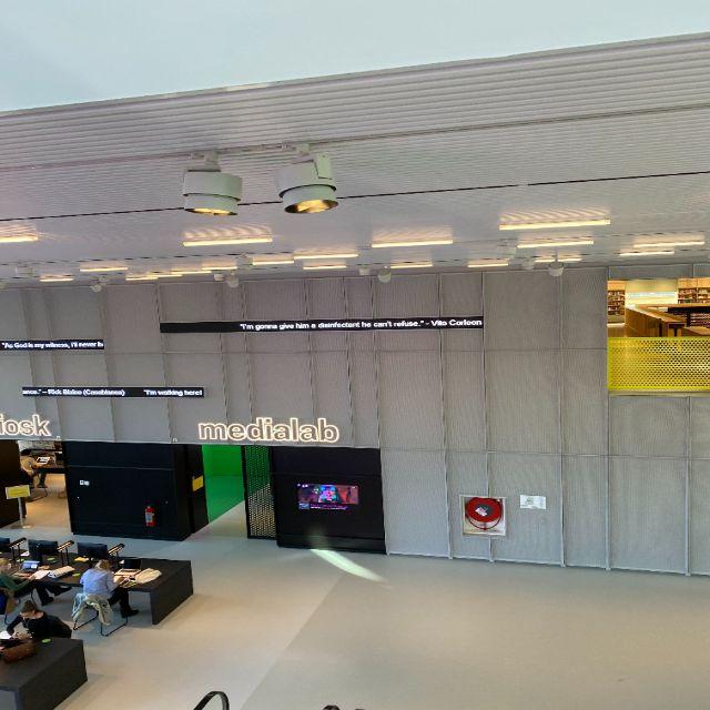 Man erkennt von einer gehobenen Perspektive aufgenommen Teile des Innenraum des Forums. AN den Wänden sind auf Leuchttafeln Sprüche oder Zitate geschrieben. Man erkennt das Medialab mit dem Greenscreen aus der Ferne und auch einen Teil des Kinderspieleparadieses.