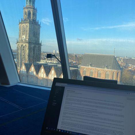 Der Fotografierende saß hinter dem aufgeklappten Laptop. Man schaut auf eine große Fensterfront. Die Scheiben sind nass, es hat geregnet. Man blickt auf einen großen Kirchturm. Dieser wird von der Sonne beleuchtet.