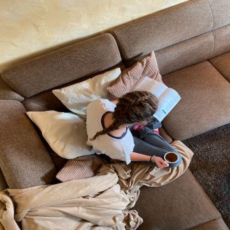 Man erkennt mich (Mädchen) aus der Vogelperspektive. In der rechten Hand halte ich eine Tasse Tee. Ich sitze im Schneidersitz auf der Couch. Auf meinem Schoß liegt mein schweres BWL Buch.