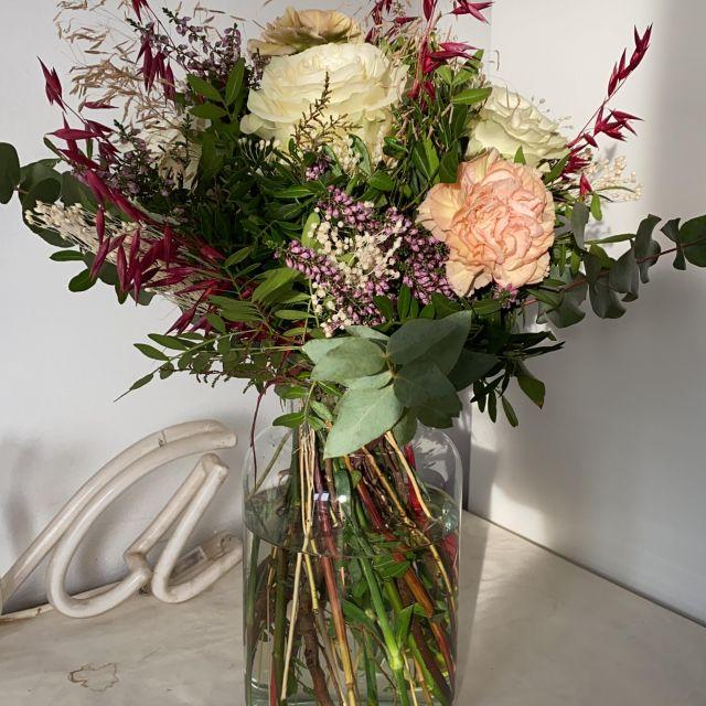 Ein Strauß Blumen in einer Glasvase steht auf dem Schreibtisch