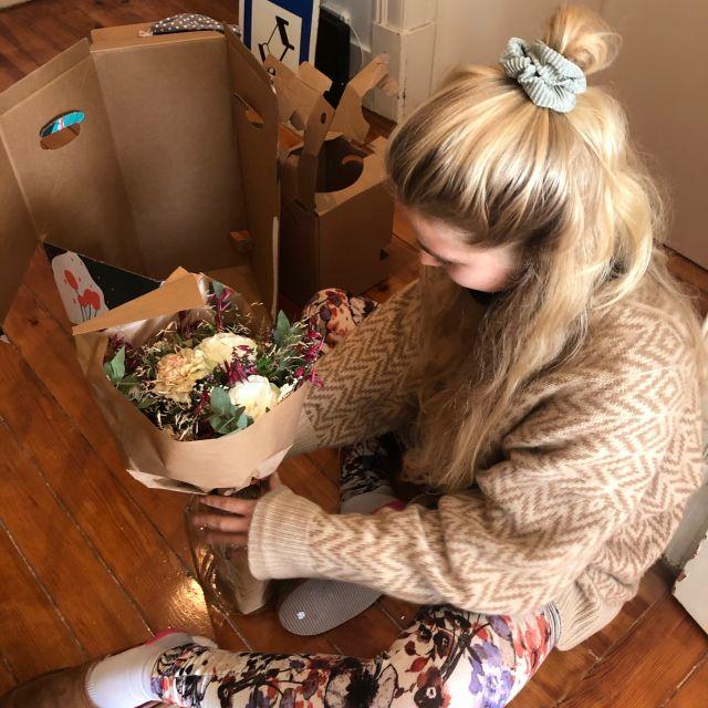 Ich sitze direkt vor der Haustür und halte meinen Strauß Blumen in der Hand.