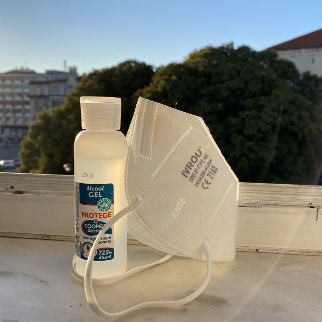 Auf dem Fensterbrett steht eine Flasche Desinfektionsmittel und eine FFP 2 Maske.