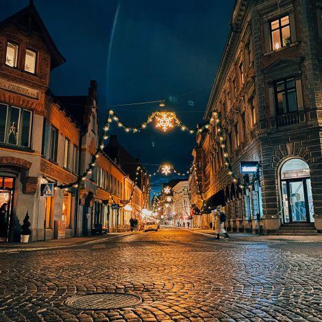 Eine Kopsteinpflasterstraße ist zur Weihnachtszeit fetslich geschmückt mit zahlreichen Girlanden, Sternen und Tannenzweigen.