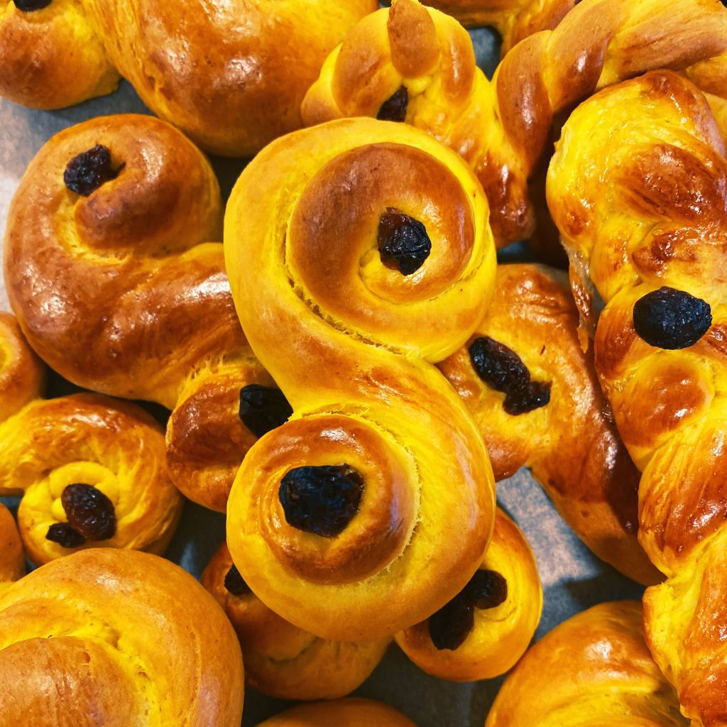 Ein großer Haufen Lussekatter, typische Brötchen die in Schweden zum Luciafest gebacken werden. Sie besteehen aus Hefeteig mit Safran. Dieser wird länglich ausgerollt und dann in eine typische S-Form gebracht. In die Mitte der zwei Kreise steckt man eine Rosine.