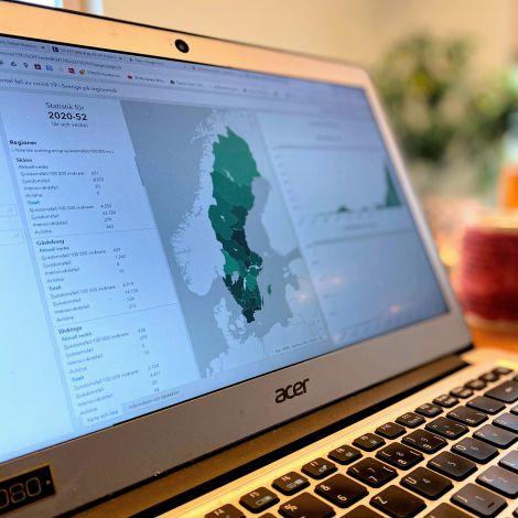 Auf einem Notebook ist eine Website des schwedischen Gesundheitsamts zu sehen. Hier sieht man eine Karte und die aktuellen Fallzahlen der Pandemie.