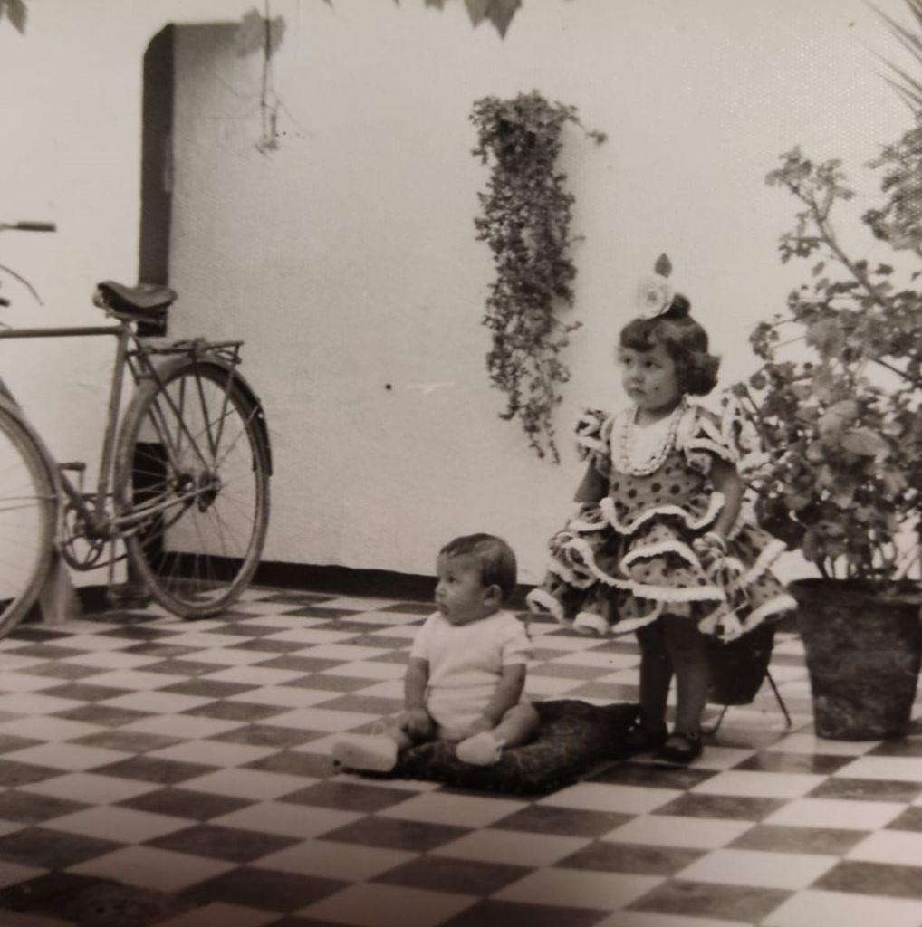 Schwarzweißaufnahme: Zwei Kleinkinder in einem Innenhof mit schwarz-weißen Fließen. Das Mädchen steht in einem pompösen Kleid.