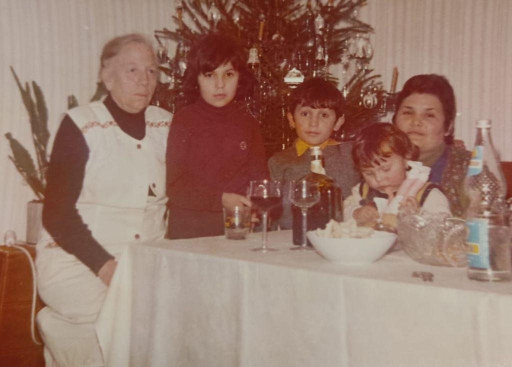 Mädchen, Junge, Kleinkind, Frau und ältere Damen an einem Tisch mit weißer Tischdecke vor einem Weihnachtsbaum.