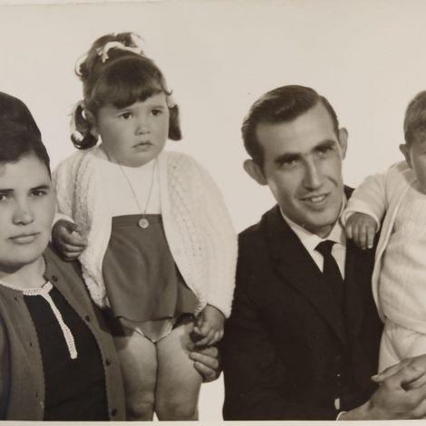 Schwarz-weiß-Aufnahme mit Mutter und Vater, elegant gekleidet, jeweils mit einem Kind auf dem Arm.