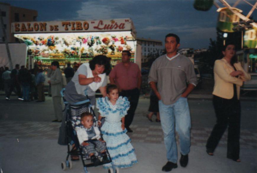 Mann, Frau, Mädchen in Sevillana-Kleid und Kleinkind in Kinderwagen vor Schießbude und Riesenrad.