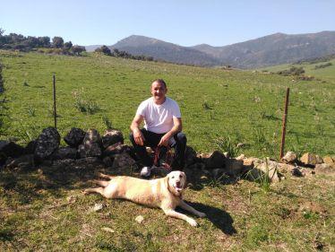 Mann sitzt in weißem T-Shirt auf einer Steinmauer vor einer Weide und Bergen, vor ihm ein beiger Labrador.