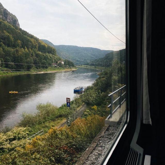 Blick aus dem Zugfenster auf einen Fluss und Berge.