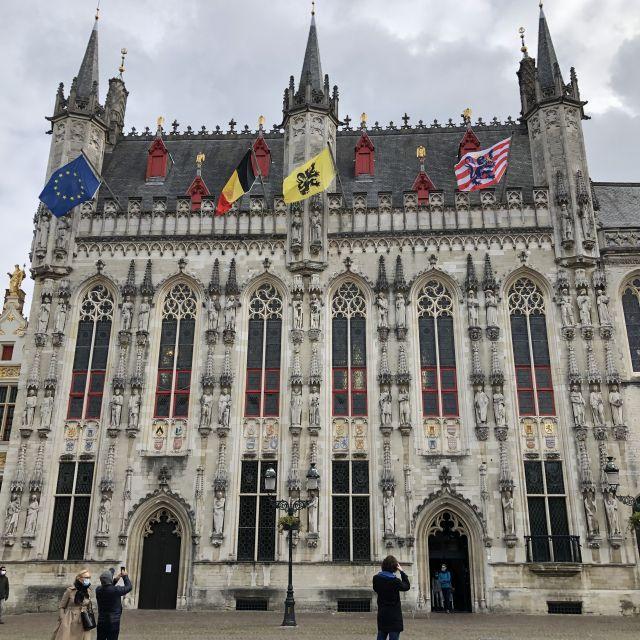 Großes helles Gebäude mit mehreren Flaggen auf dem Dach.
