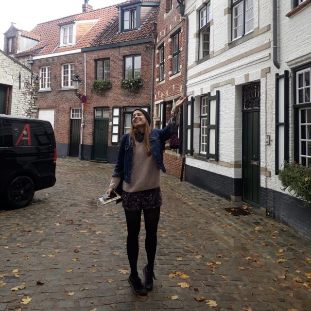 Winkendes Mädchen in einer Stadt mit Häusern im Hintergrund.
