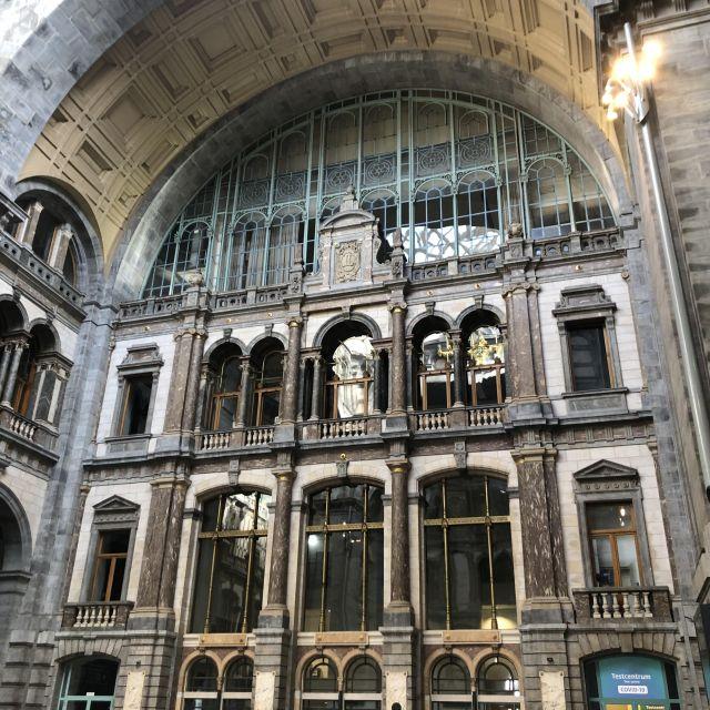 Imposante Eingangshalle mit langen Säulen auf mehreren Ebenen.