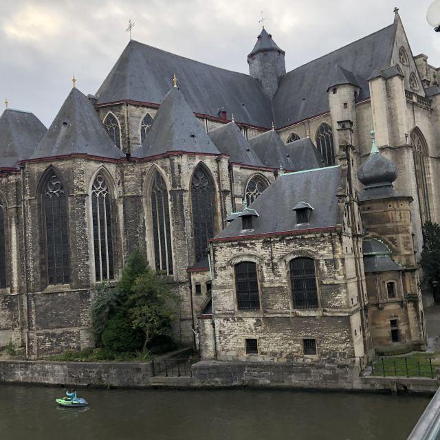 Eine große alte Steinkirche von hinten direkt am Fluss gebaut. Das Dach ist grau-bläulich und der Stein ist zwar hell, aber man erkennt die Alterserscheinungen, da sich die Fassade dunkel verfärbt.