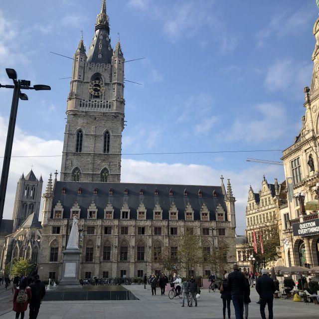 Blick auf ein typisch belgisches Gebäude, der Belfried. Zu einem fünfstöckigen Haus gehört ein hoher viereckiger Turm mit kleinen Türmen an jeder Ecke und spitzen Dächern.