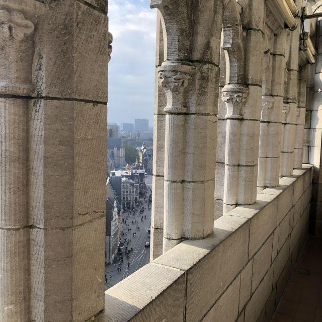 Auf dem Bild befinden wir uns oben auf einem Turm der mit einer hellen Steinmauer und Säulen abschließt.