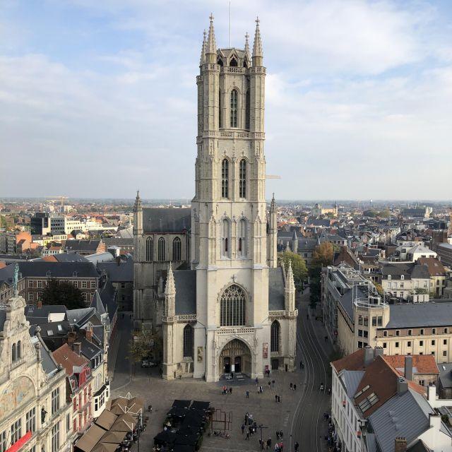 Der Blick geht von oben auf die gegenüber stehende Kathedrale. Die Kathedrale hat einen großen Turm aus hellen Stein. Rings herum befinden sich Gebäude.