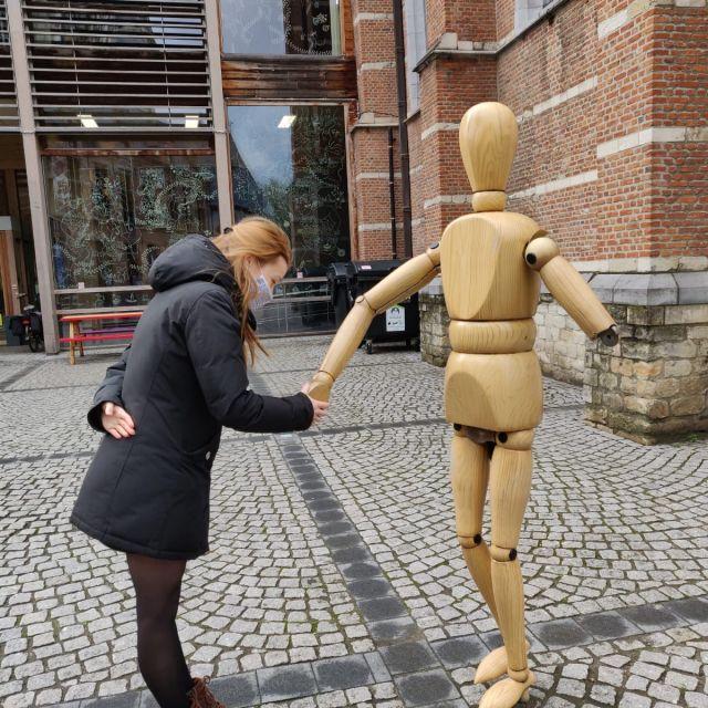 Eine Frau und eine Holzfigur schütteln Hände