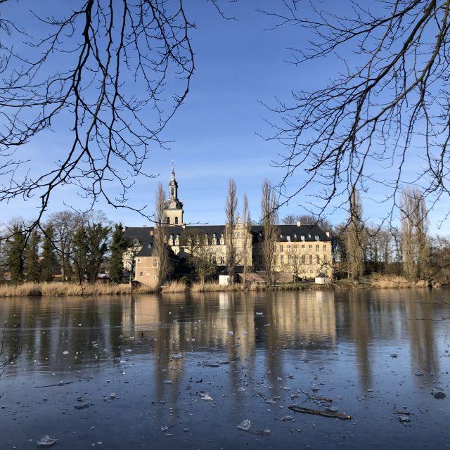 im Vordergrund ein See im Hintergrund ein alter Gebäudekomplex.