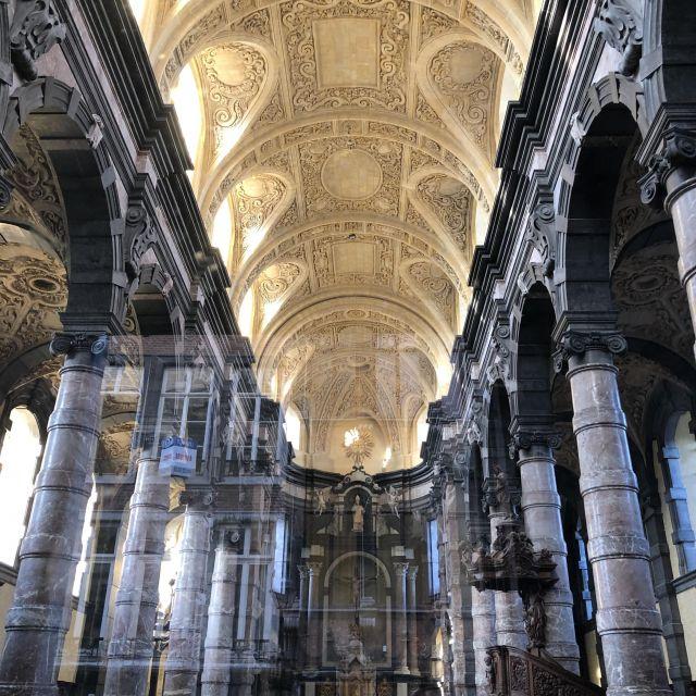 Helle, verzierte Kirchendecke mit dunklen Säulen.