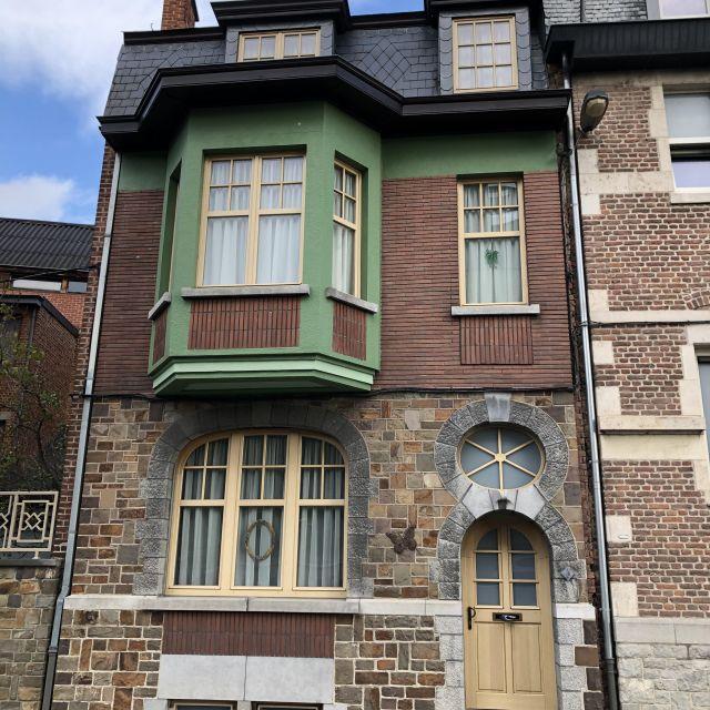 Ein Steinhaus mit grünen Fensterrahmen.