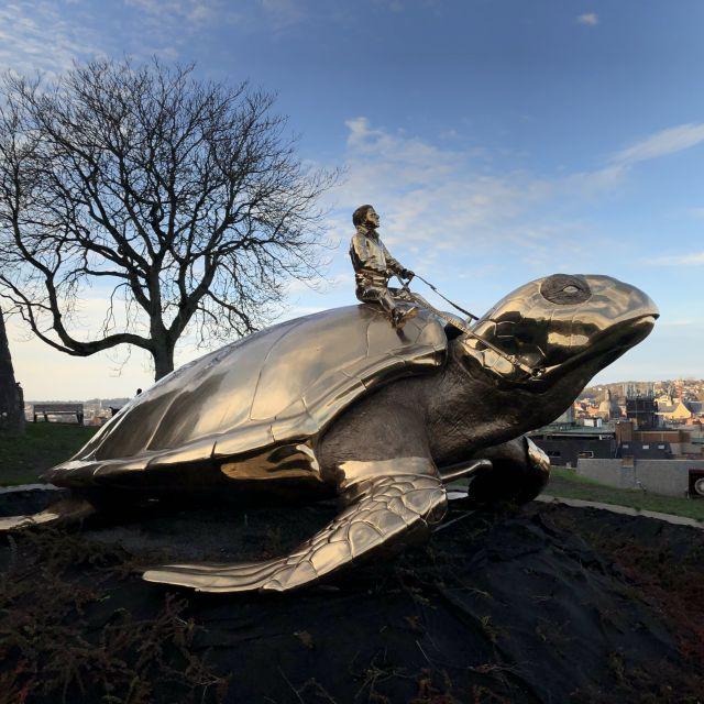 Auf einer großen Bronzeschildkröte sitzt ein kleiner Mann.