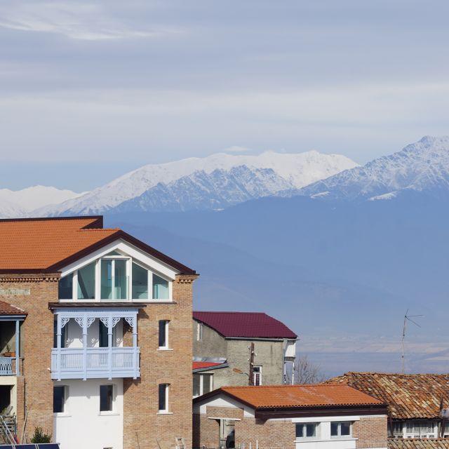 Gebäude in der Altstadt mit Balkon, Caucasusgebirge im Hintergrund
