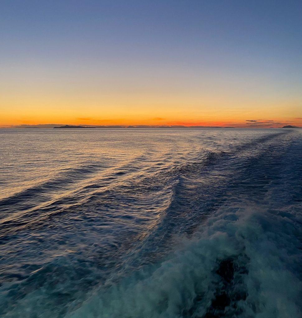 Zu sehen ist ein Sonnenuntergang von der Fähre aus im Ägäischen Meer.