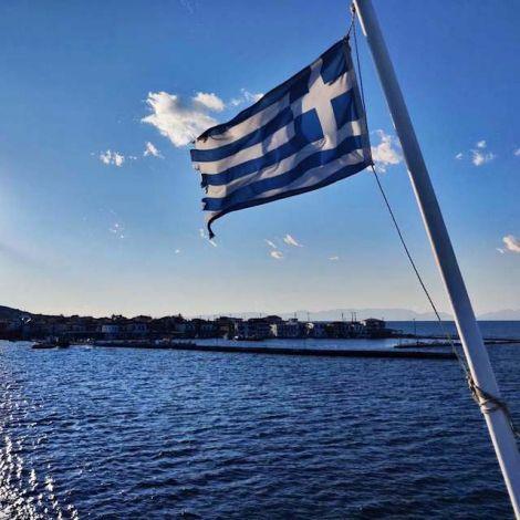 Im Vordergrund weht die griechische Flagge. Im Hintergrund befindet sich das Meer und ein kleiner Hafen.