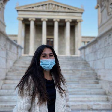 Im Vordergrund bin ich mit meiner Maske zu sehen und lächle in die Kamera. Im Hintergrund ist die Nationalbibliothek Athens zu sehen.