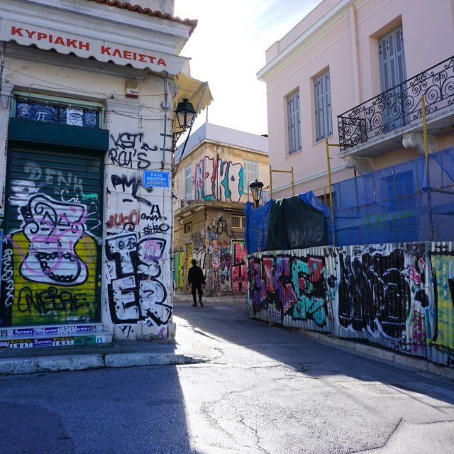 Auf dem Foto sind drei mit Graffiti beschmierten Häuserwände zu sehen, zwischen welchem sich ein Mann befindet, der durch die Gassen Athens spaziert.