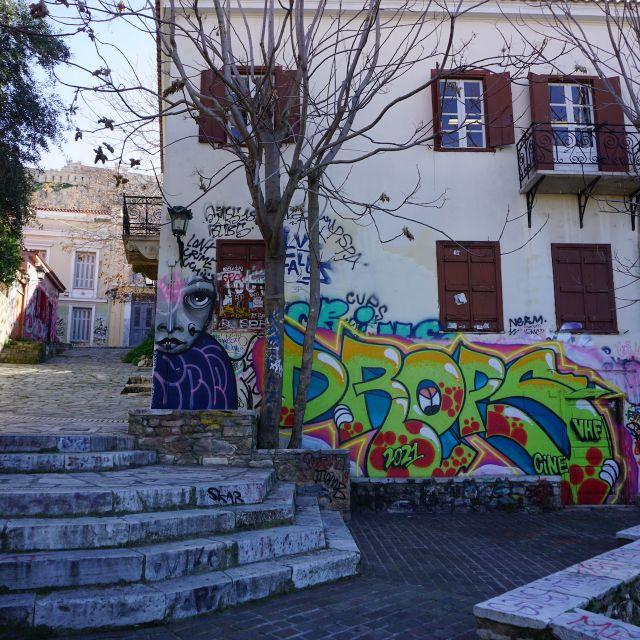Auf dem Foto ist eine Hauswand in Athen zu sehen, welche mit bunten und verschiedenen Graffiti Schriftzügen beschmiert wurde. Im Hintergrund ist der Ansatz der Akropolis auf dem Berg zu sehen.