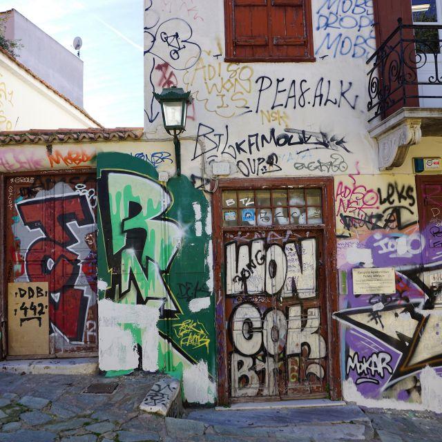 Auf dem Foto ist eine Hauswand in Athen zu sehen, welche mit bunten und verschiedenen Graffiti Schriftzügen beschmiert wurde.
