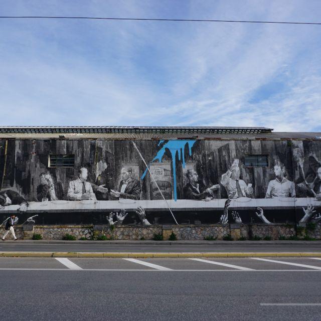 An der großen Wand vor der Hauptstraße ist ein weiteres Kunstwerk zu sehen. Es zeigt Politiker, die zusammen am Tisch sitzen und miteinander kommunizieren, während unter ihnen Hände nach ihnen greifen.