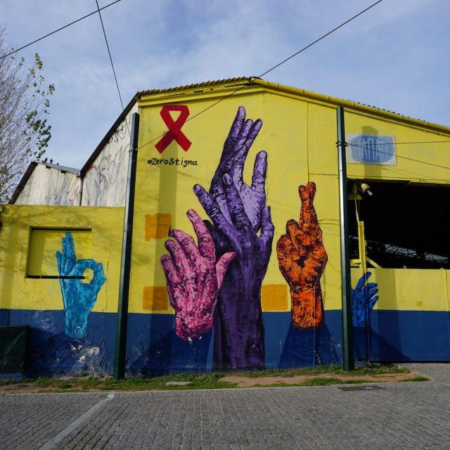 Bunte und große Hände, die auf einem gelben Hintergrund einer Hauswand gemalt worden sind. Die Hände haben alle unterschiedliche Farben und zeigen verschiedenen Symbole mit ihren Fingern.