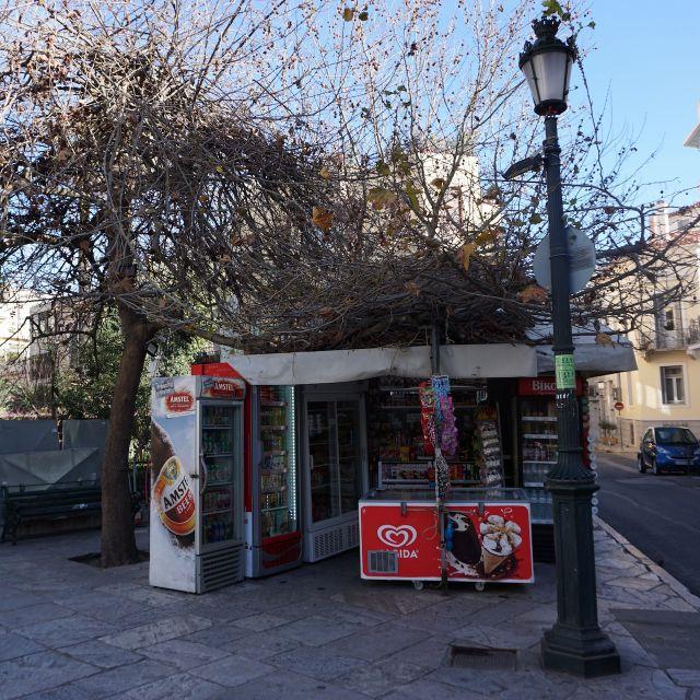 Auf dem Foto ist ein kleiner Kiosk zu sehen. Er befindet sich mitten auf dem Bürgersteig. Auf der rechten Seite ist die Straße mit Autos zu erkennen.