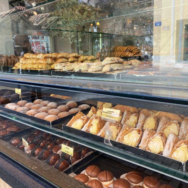 Auf dem Foto ist das Schaufenster einer griechischen Bäckerei zu sehen. Die Bleche sind voll von verschiedenen Kuchen und Törtchen.