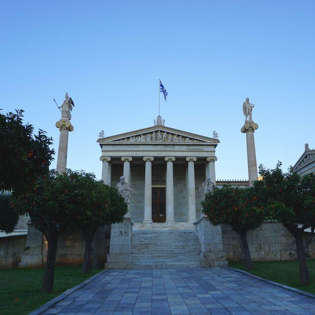 Auf dem Foto befindet sich die Nationale und Kapodistrias-Universität von Athen. Im Vordergrund sieht man den Weg, der zur Uni führst, umgeben von Orangenbäumen.