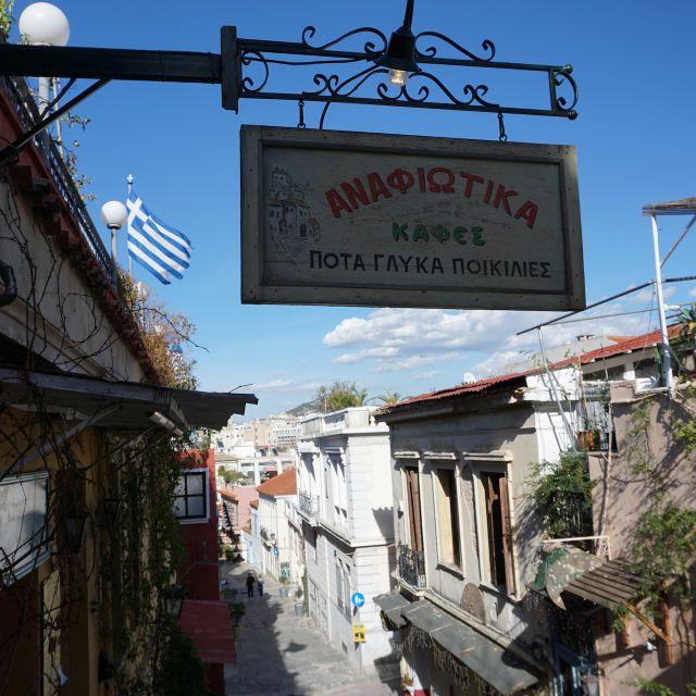Im Vordergrund hängt ein Schild mit der griechischen Aufschrift eines Cafés. Im Hintergrund weht die griechische Flagge zwischen den engen Gassen des Stadtviertels Plaka. Die Sonne scheint, weshalb der Himmel besonders blau erscheint und die Häuser vom Sonnenlicht beleuchtet sind.