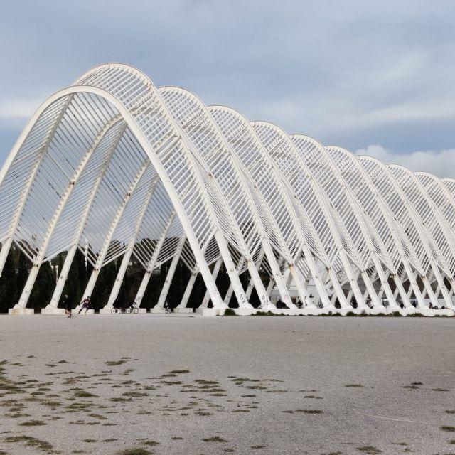 Im Vordergrund ist ein weißer großer Rundbogen zu sehen, welcher auf dem großen Gelände des Olympiastadions steht.
